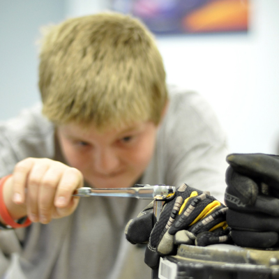 Student using ratchet to loosen engine bolt in mechanical engineering summer camp