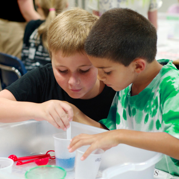 Two boys mix chemicals into a pH indicator solution in the chemical engineering camp